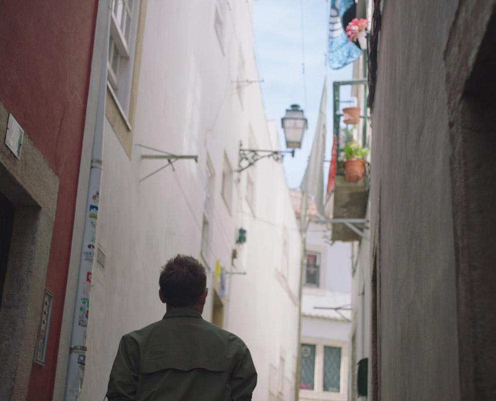 Back of man walking through alleyway