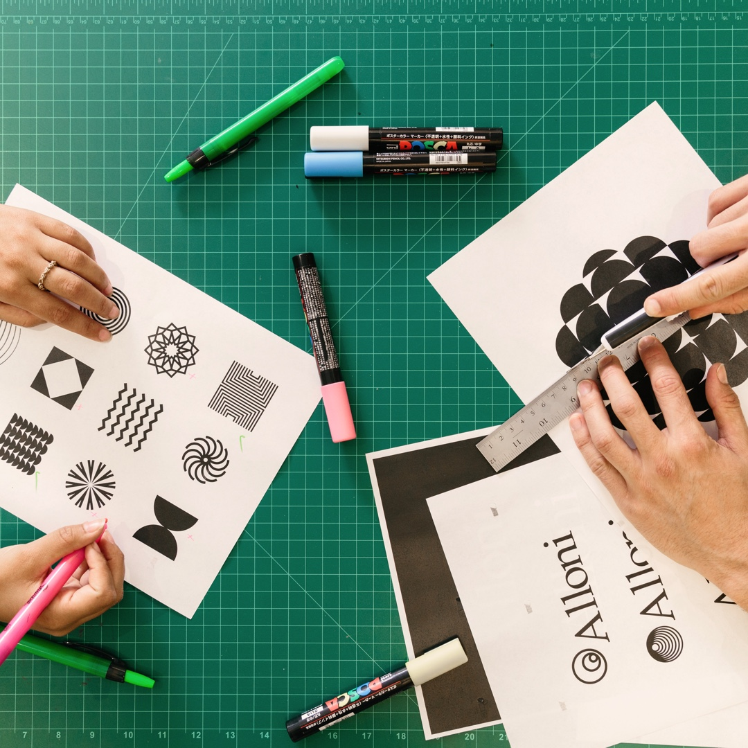 Two peoples' hands working on printed illustrations on top of design cutting mat