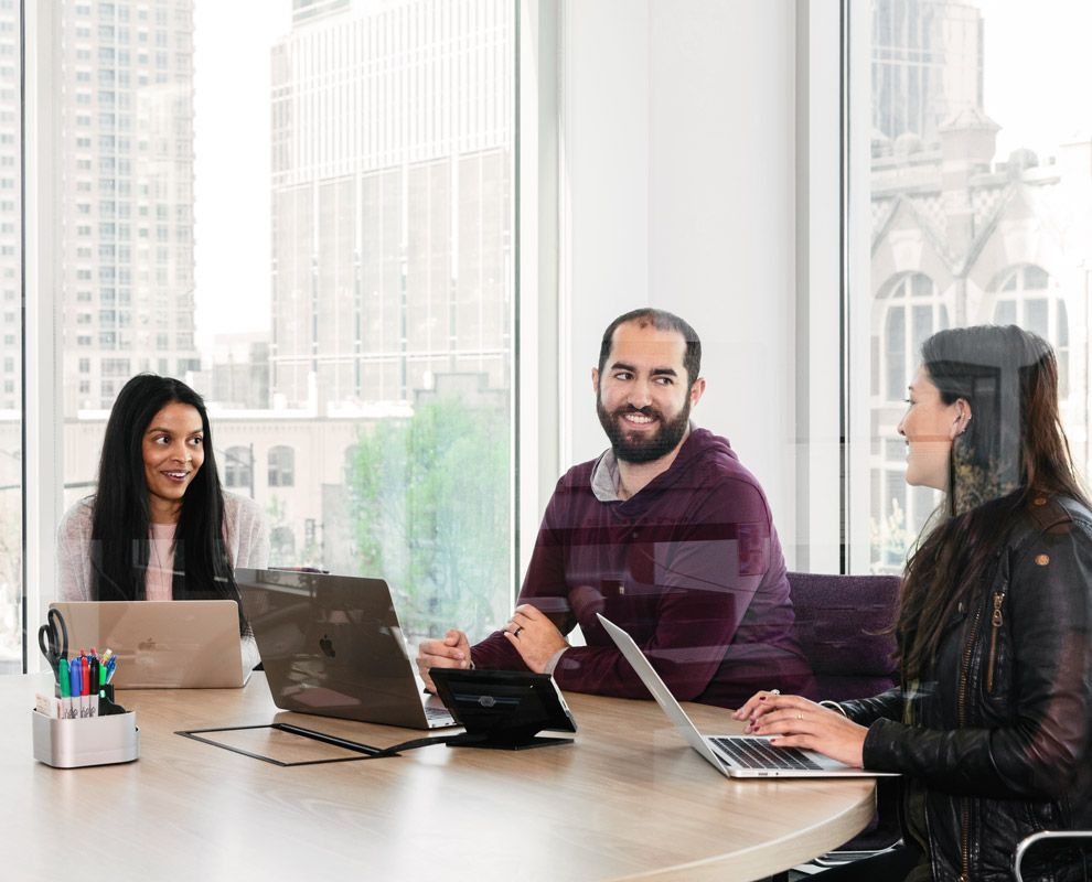 Three people sitting at table in front of laptops in conference room