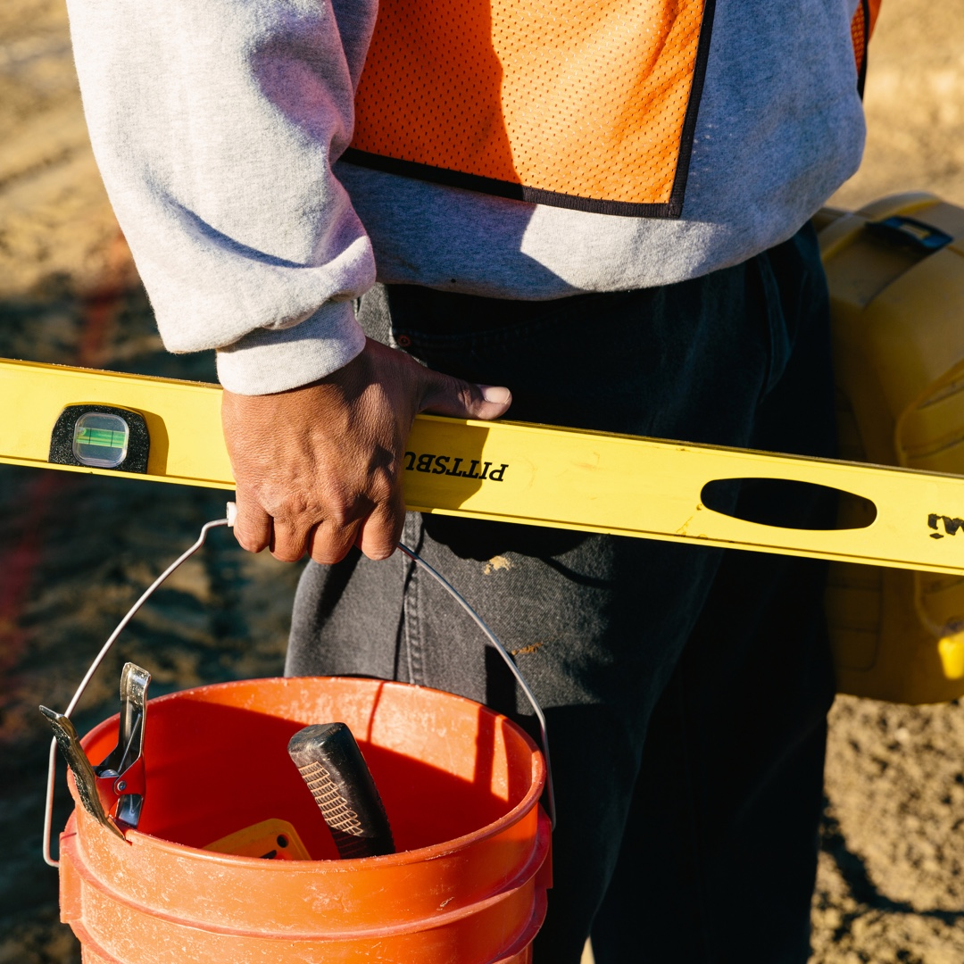 Construction worker shown at waist holding spirit level and bucket of tools