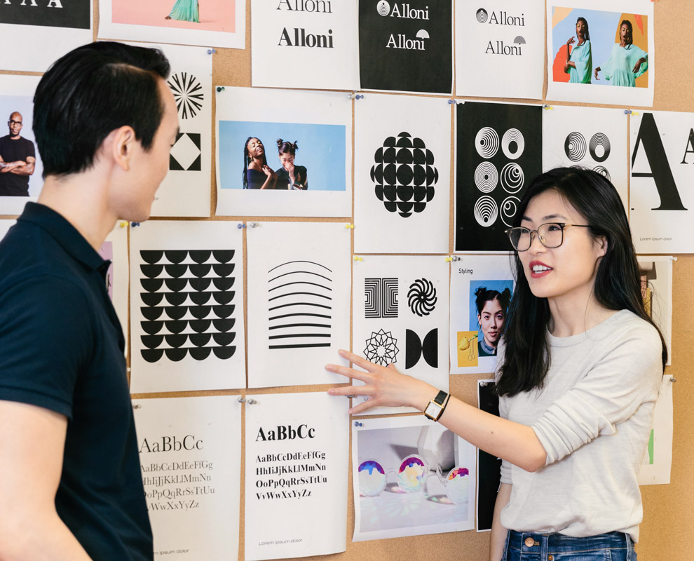 Woman and man talking in front of corkboard wall covered with photographs, designs, and typography