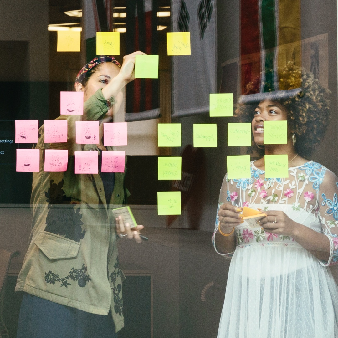 Two women placing brainstorming sticky notes on window