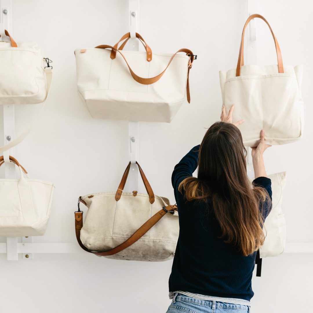 Woman shown from behind reaching for a tote bag hanging on a shelf