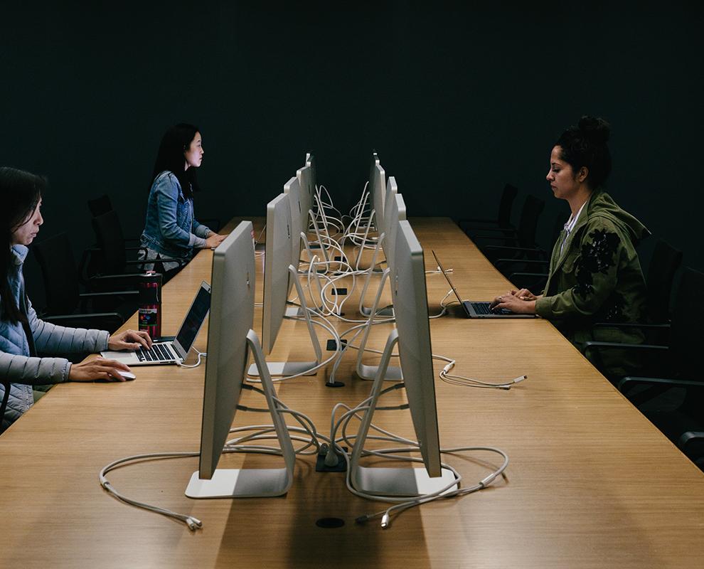3 orang bekerja di komputer dalam ruang pejabat kongsi