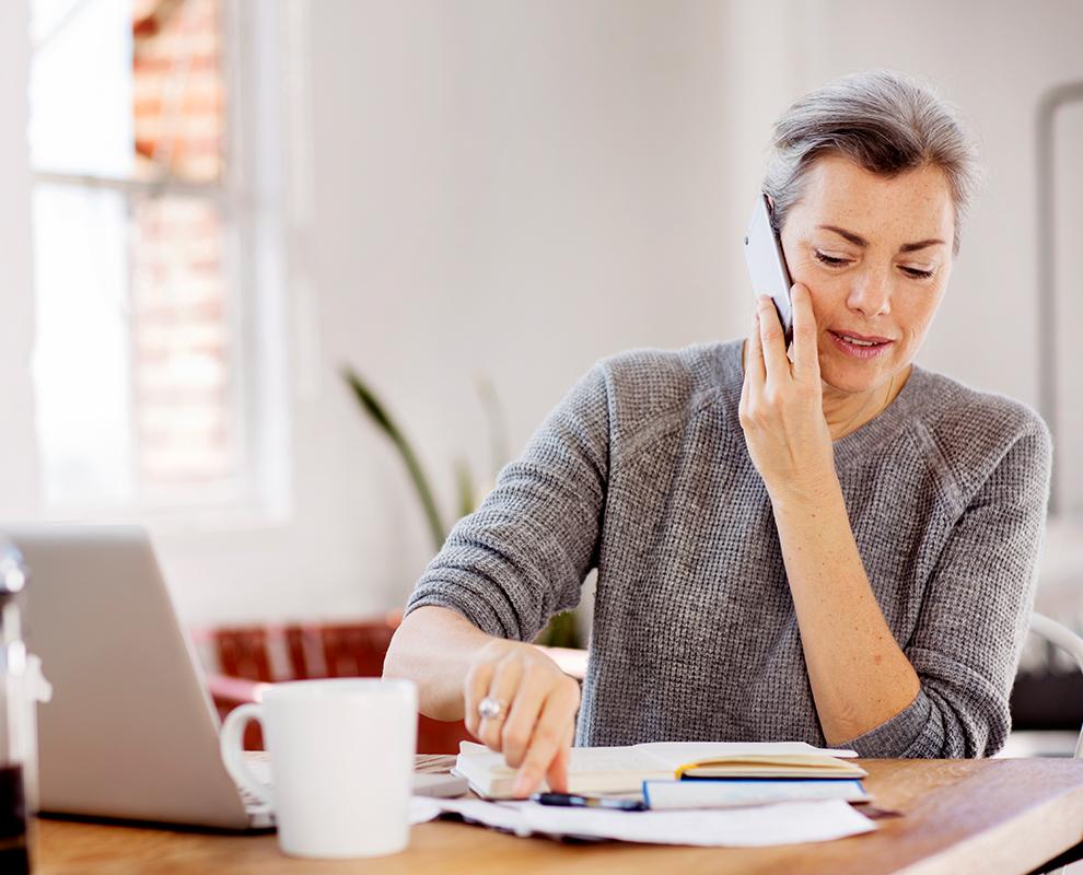 ノート パソコンの前に座り、スマートフォンで話している女性